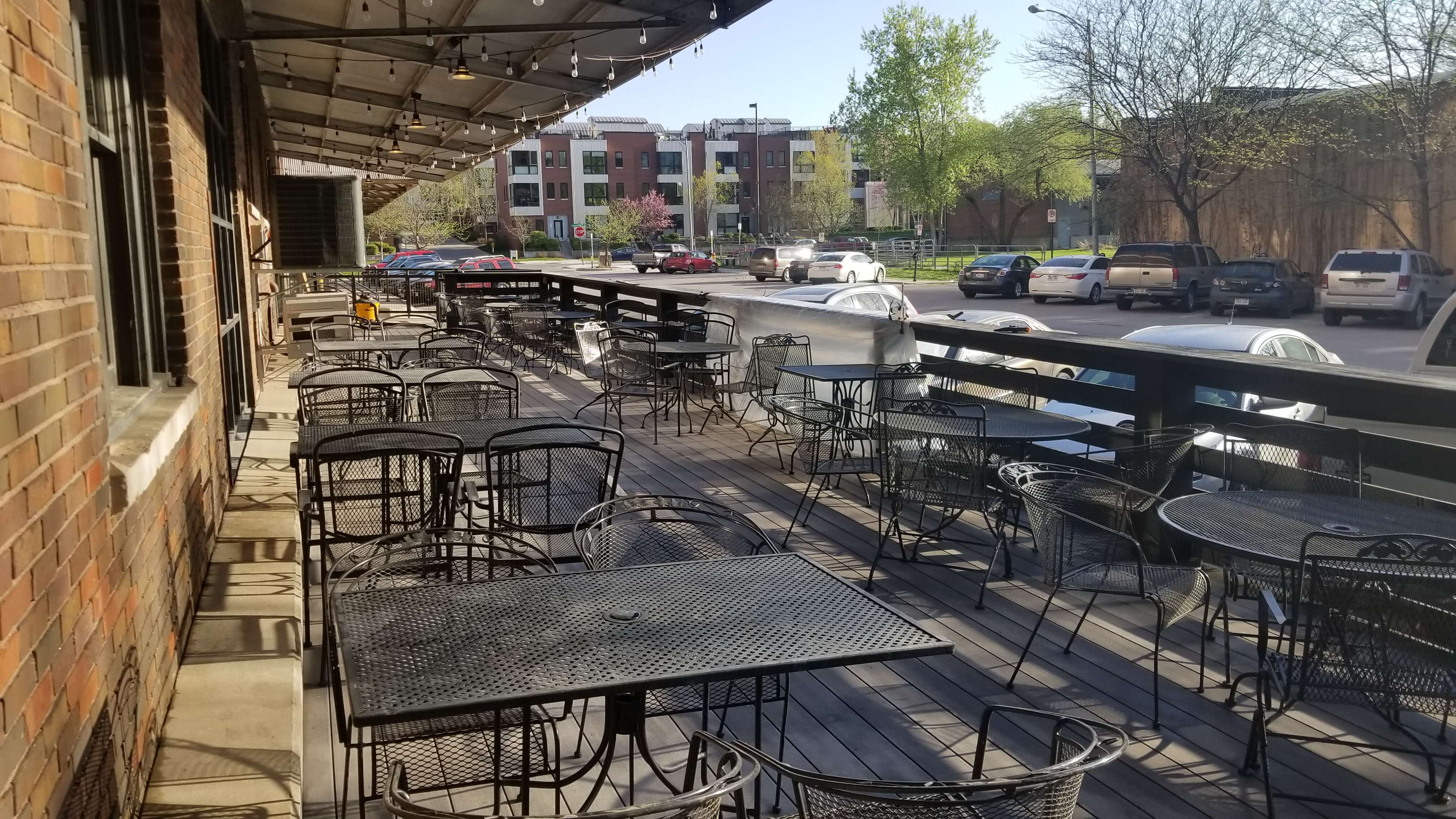 Deck Full of Black Metal Table and Chairs Next to a Downtown Road Lined with Parked Cars