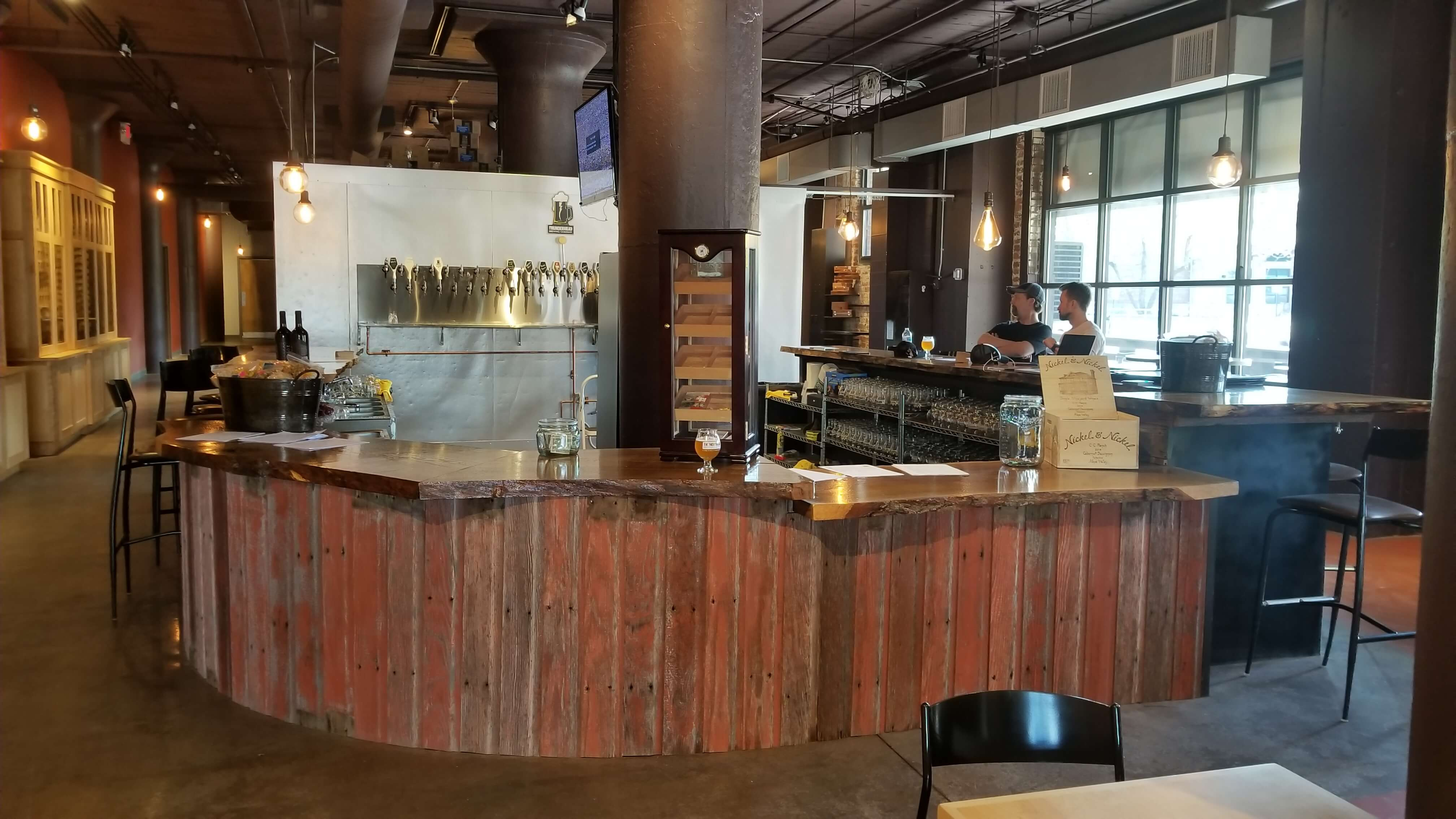 Live Edge Wood Bar with Reclaimed Wood Panels and a Metal Beer Tap Wall Behind It