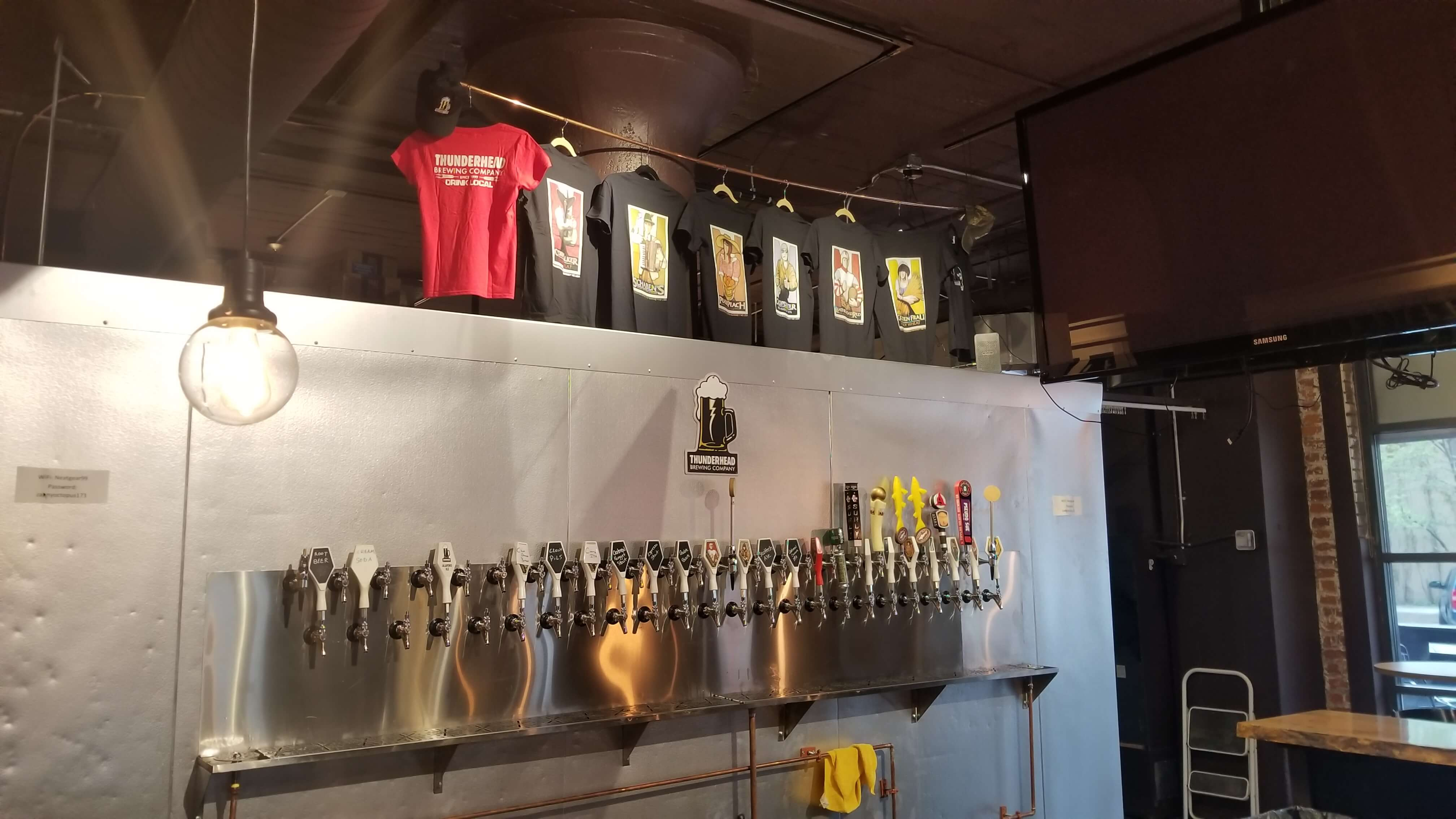 Metal Beer Tap Wall with Thunderhead Brewing Shirts Hanging Above It